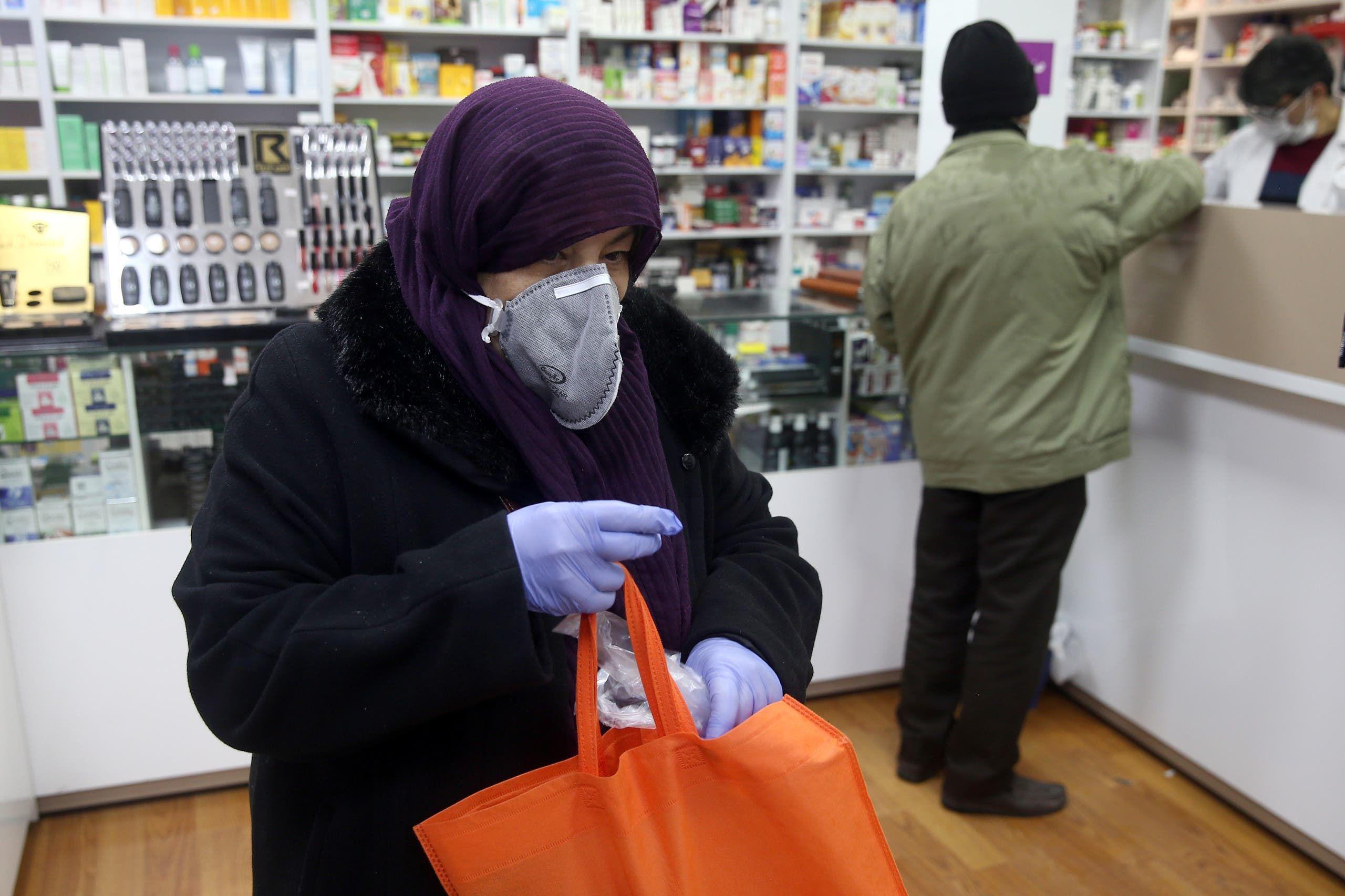 إيرانية ترتدي كمامة وفاذات طبية في صيدلية في طهران خشية من كورونا