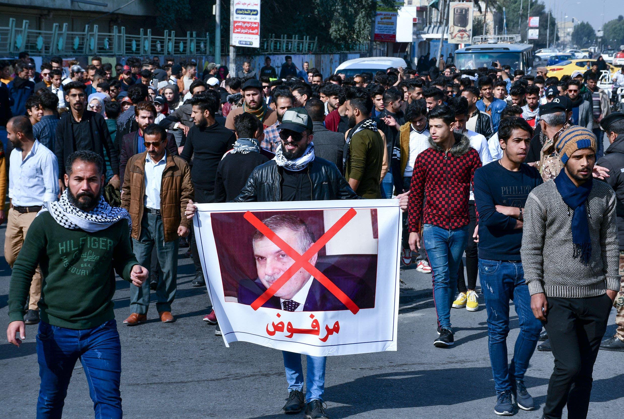 متظاهرون يرفعون صور لعلاوي تعبيراً عن رفضهم تكليفه (أرشيفية- فرانس برس)