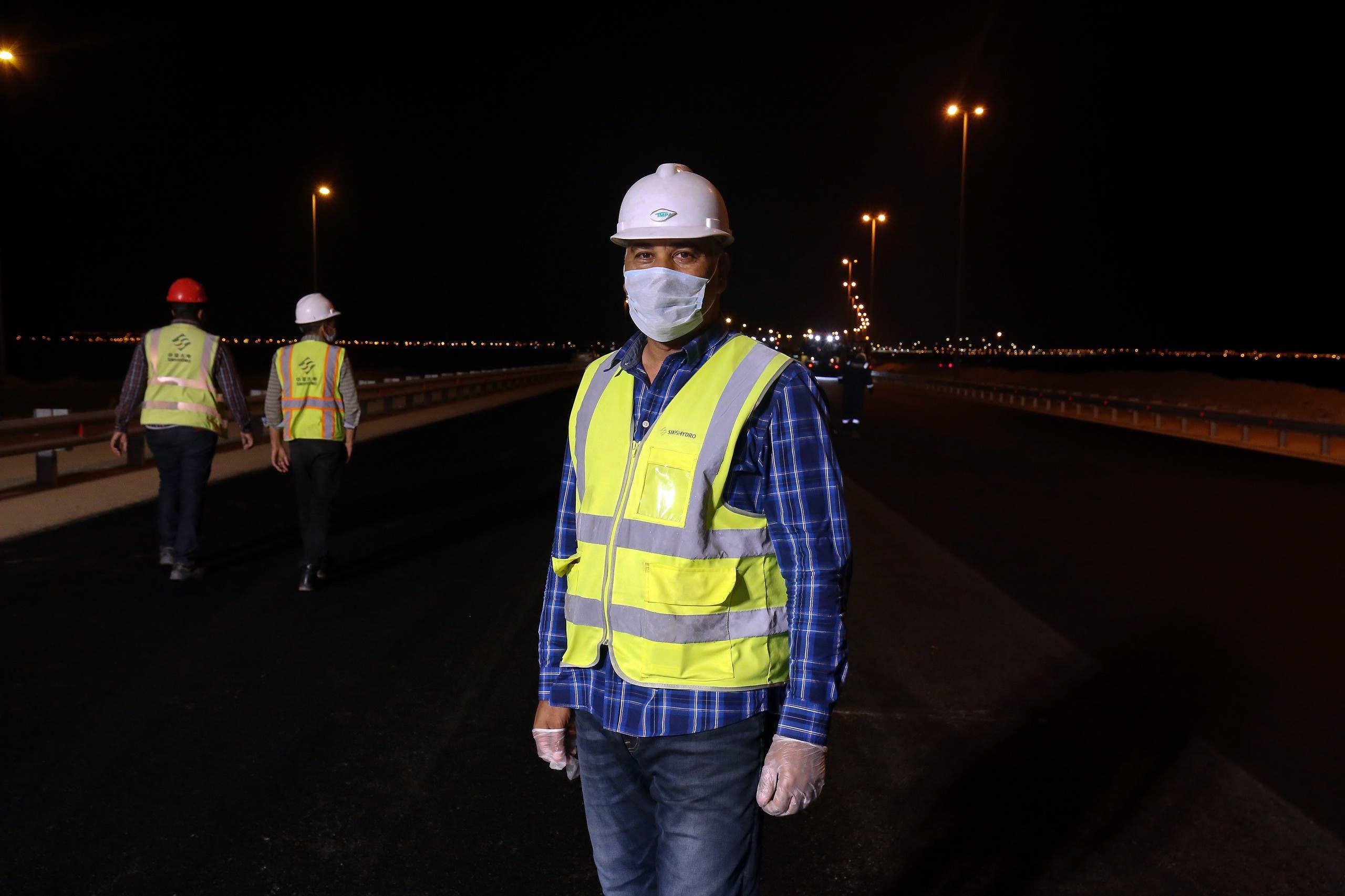 مهندس كويتي يرتدي كمامة ويشرف على أعمال تعبيد الطرقات ليلاً في العاصمة