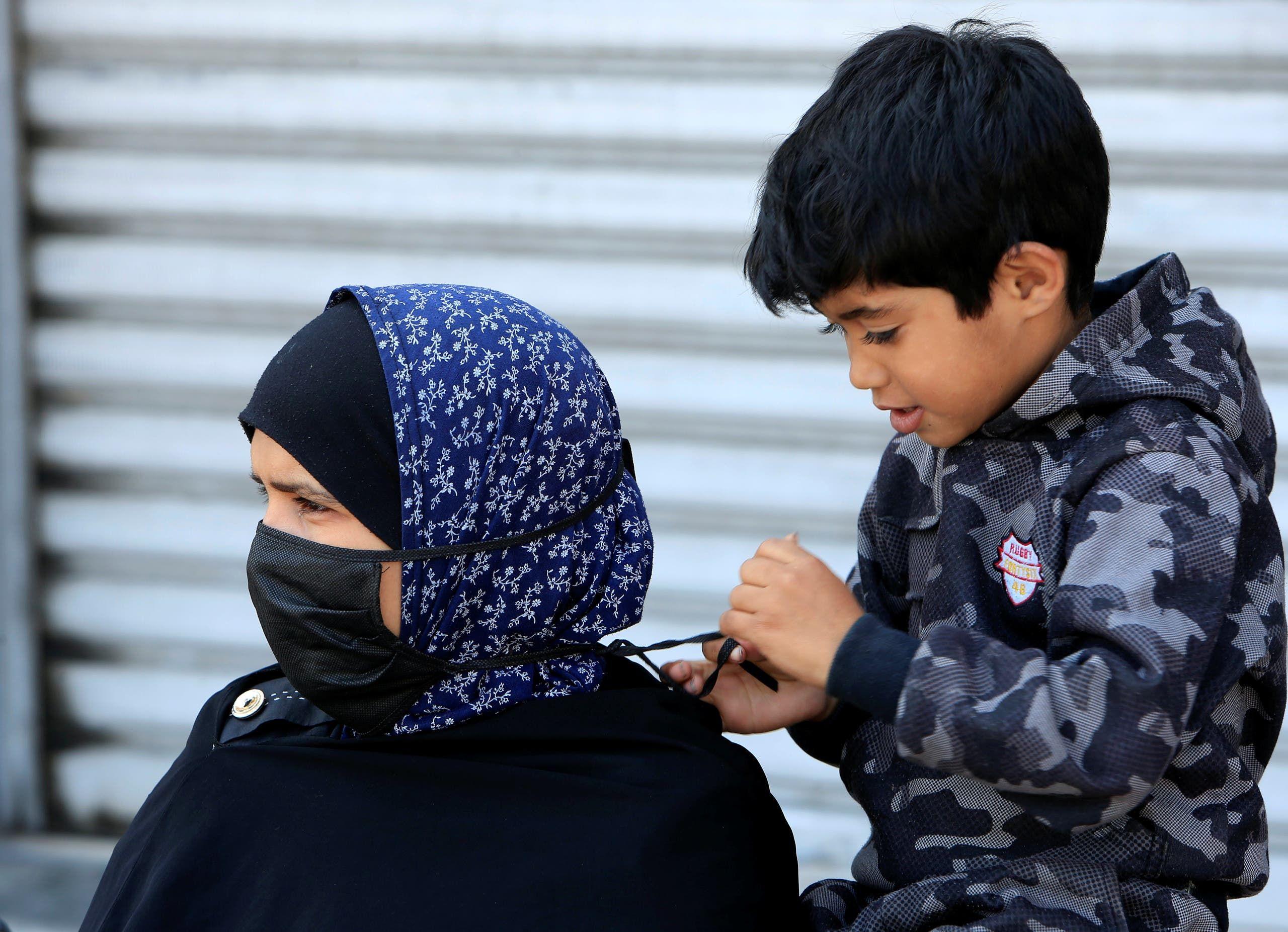 طفل يساعد والدته على ارتداء الكمامة في صيدا بجنوب لبنان