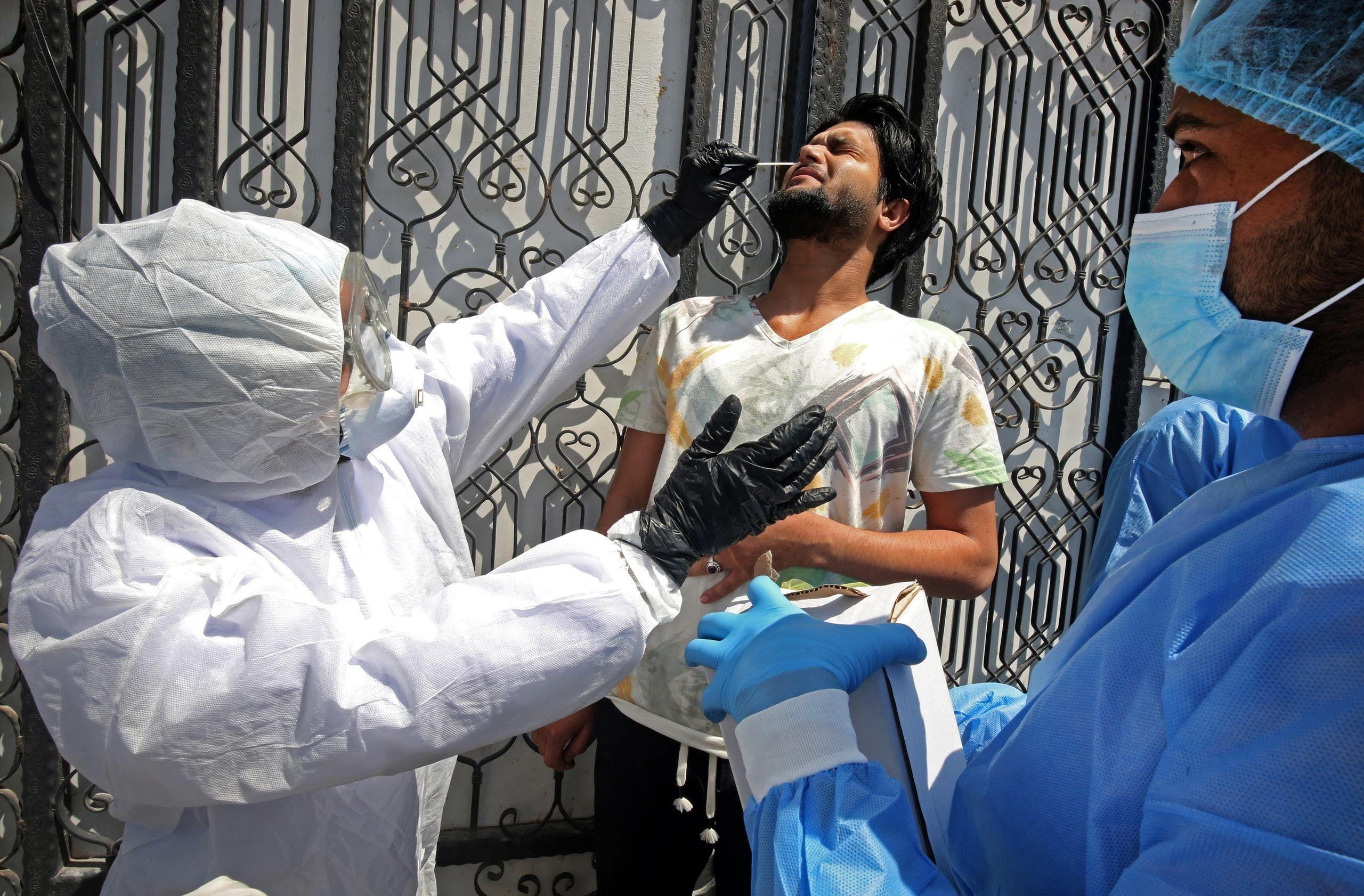 أطباء متخصصون في مستشفى عام عراقي يختبرون أحد السكان في ضاحية مدينة الصدر في بغداد يوم 2 أبريل (فرانس برس)