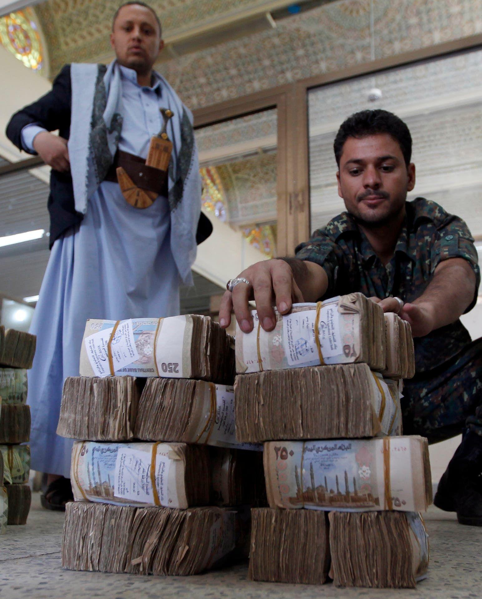 عناصر من الحوثيين يقفون أمام رزم من الريال اليمني