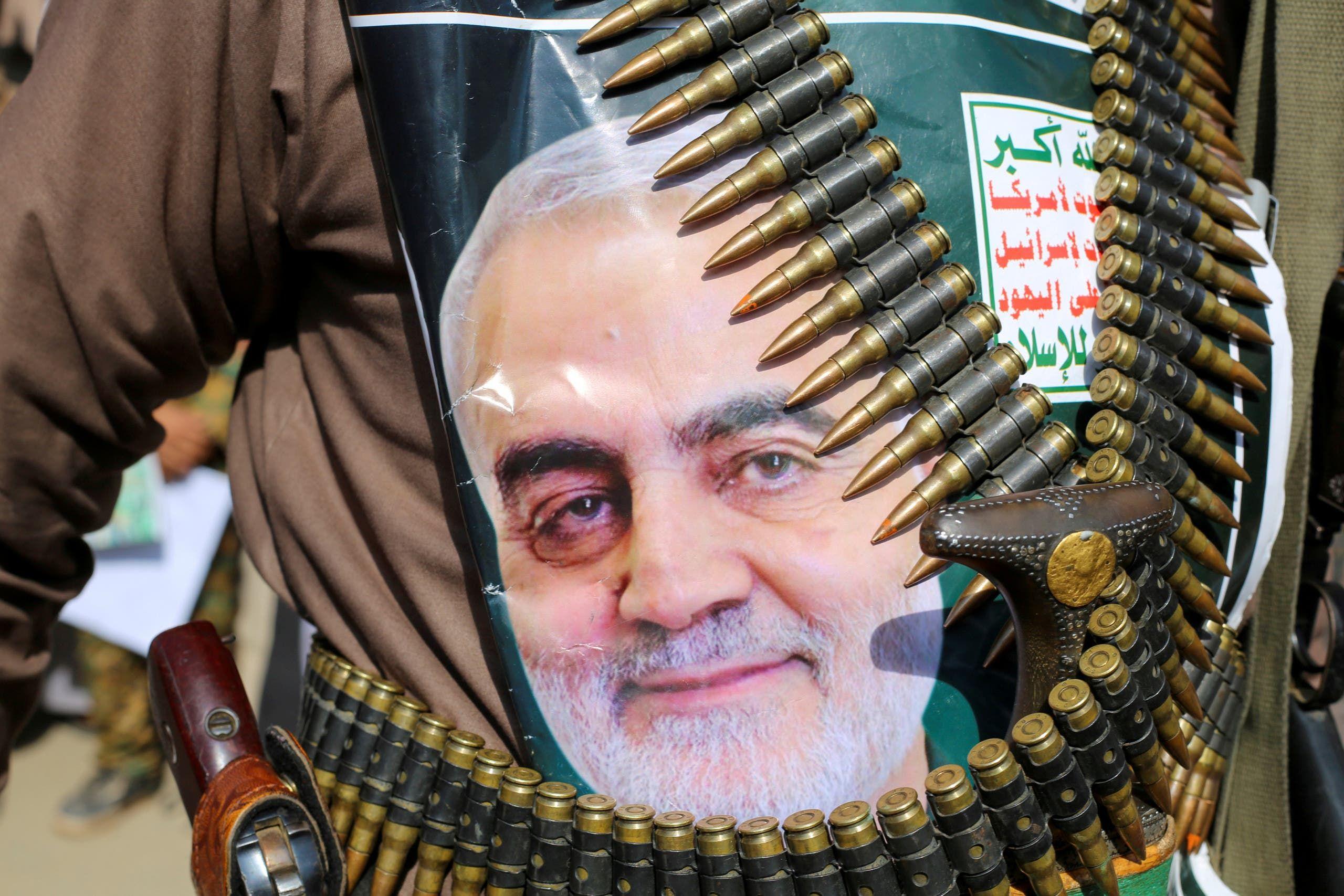 مقاتل حوثي في صنعاء يرفع صورة قائد فيلق القدس الإيراني قاسم سليماني على ظهره إلى جانب الأسلحة