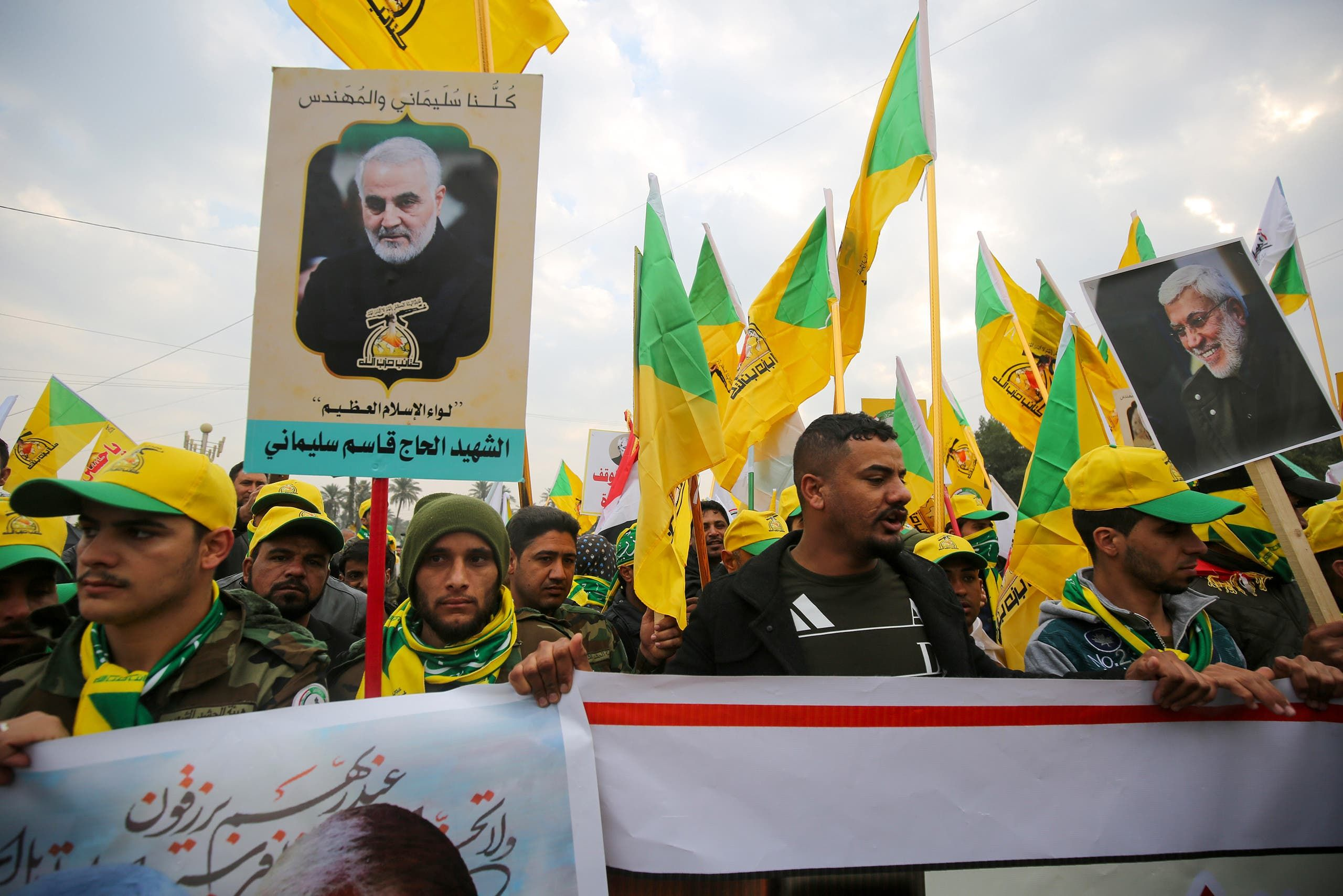 Supporters of the Hashed al-Shaabi paramilitary force and Iraq's Hezbollah brigades attend the funeral of Iranian military commander Qasem Soleimani (portrait) and Iraqi paramilitary chief Abu Mahdi al-Muhandis (portrait) in Baghdad's district of al-Jadriya, in Baghdad's high-security Green Zone, on January 4, 2020. Thousands of Iraqis chanting Death to America joined the funeral procession for Iranian commander Qassem Soleimani and Iraqi paramilitary chief Abu Mahdi al-Muhandis, both killed in a US air strike. The cortege set off around Kadhimiya, a Shiite pilgrimage district of Baghdad, before heading to the Green Zone government and diplomatic district where a state funeral was to be held attended by top dignitaries. In all, 10 people -- five Iraqis and five Iranians -- were killed in Friday morning's US strike on their motorcade just outside Baghdad airport.