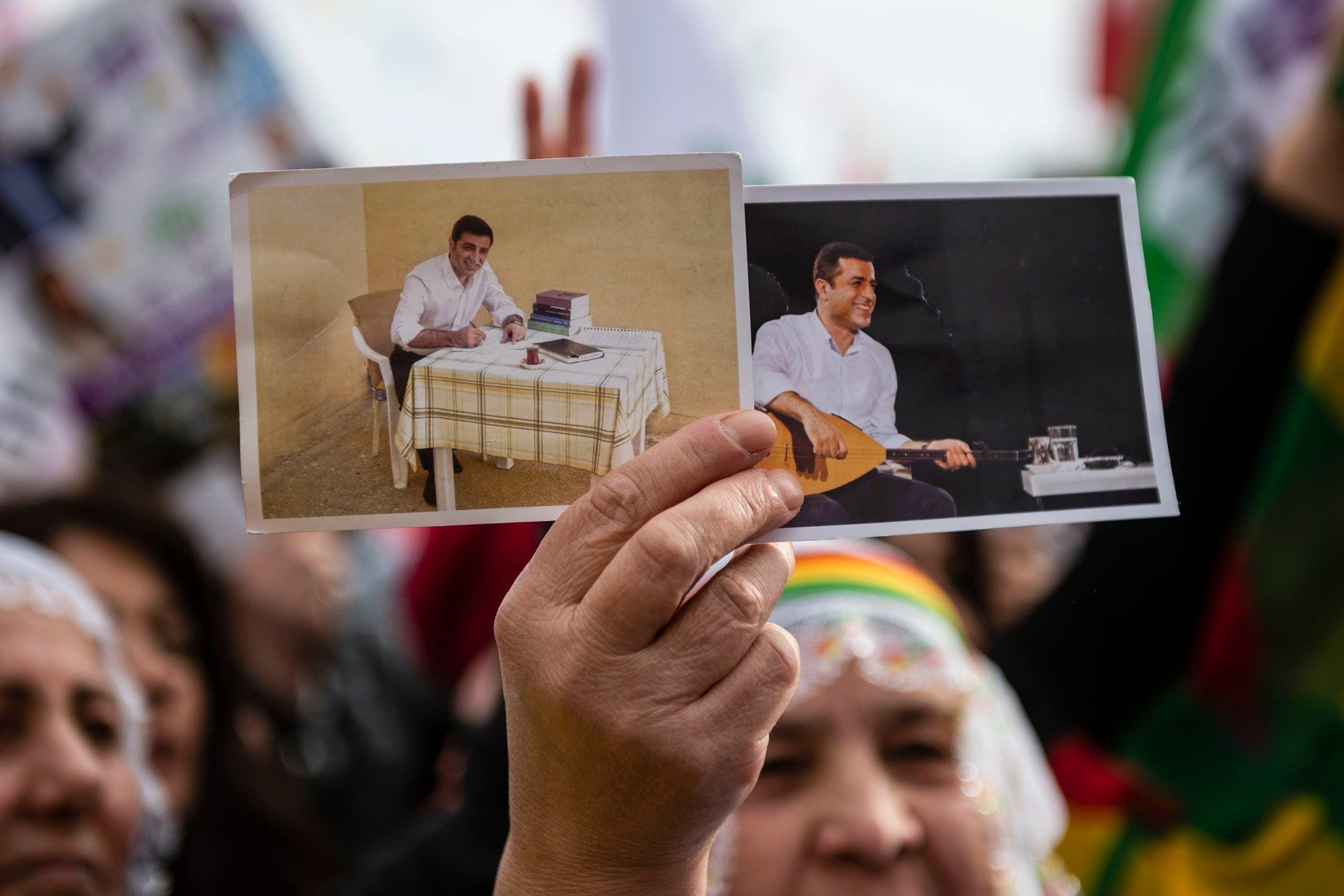 أحد مناصري حزب الشعوب الديمقراطي يحمل صورة دميرتاش أثناء حضوره تجمعاً لـ