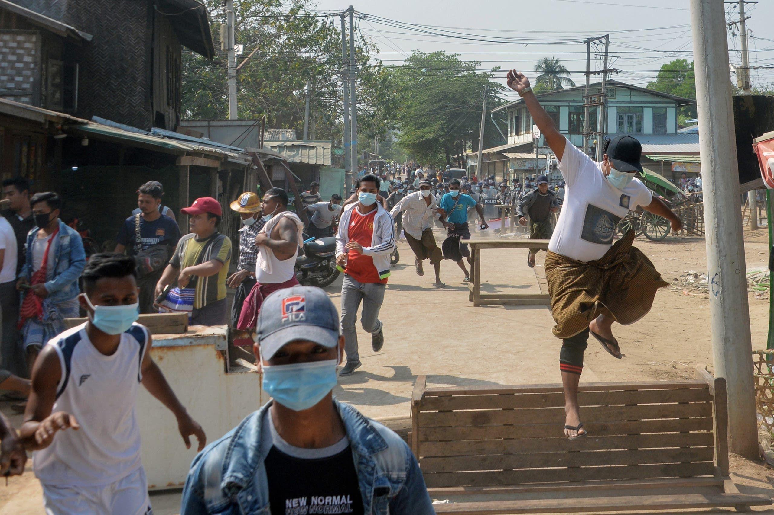 متظاهرون ضد الاانقلاب يفرون من الشرطة في إحدى مدن ميانمار أمس الجمعة
