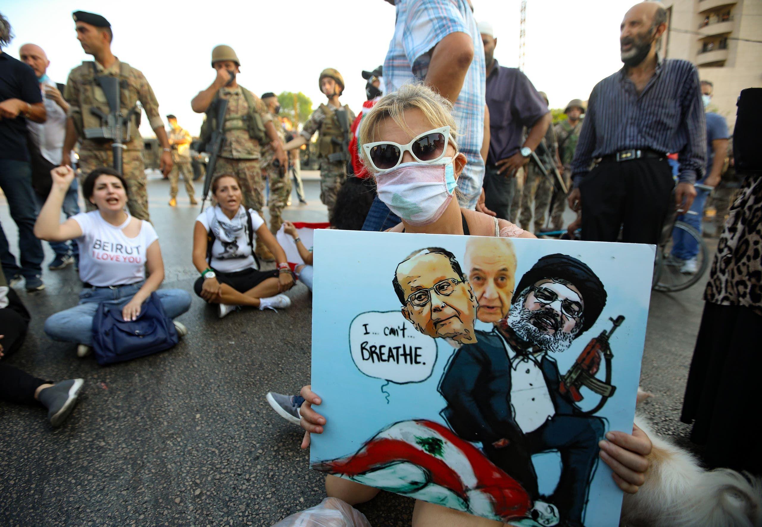 متظاهرة تحمل رسما يظهر زعيم حزب الله والرئيس اللبناني ميشال عون ورئيس البرلمان نبيه بري جاثمين على العلم اللبناني (أرشيفية فرانس برس)
