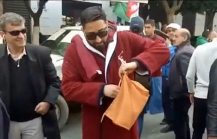 بالفيديو.. لماذا ارتدى هذا الشخص برنس الحمام وحمل شامبو وسط مظاهرات الجزائر؟
