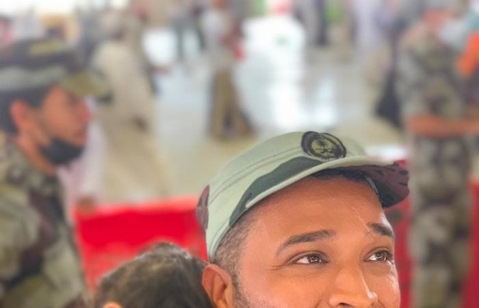 الخليح | رجل أمن سعودي يحمل طفلة أثناء رمي أهلها للجمرات